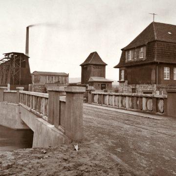 Anschlussgleis der Papierfabrik Kämmerer. Links ist die Entladestation für Kohlenwaggons zu sehen, an der ein Greifer die Kohlen aus dem Waggon hob und in Kübel einer Transporteinrichtung lud. Die Kübel konnten dann per Hängebahn zu den Verbrauchsstellen transportiert werden. Um 1924.