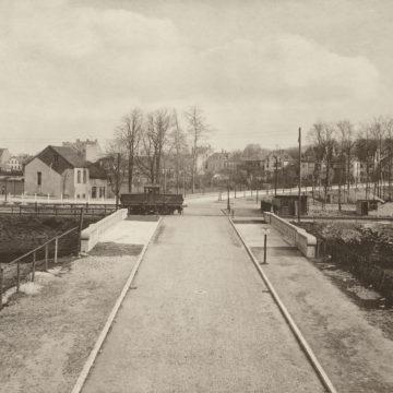 Das Anschlussgleis der Hafenbahn am Straßenzug Wachsbleiche. Im Hintergrund ist die Bebauung an der Bramscher Straße zu sehen. Um 1920.